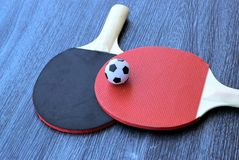 Football with table tennis rackets royalty free stock images
