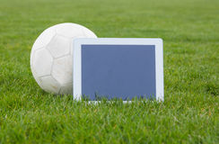 Football and tablet with blank screen on pitch Royalty Free Stock Photography