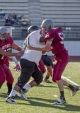Football Tackle. High school football players tackle each other royalty free stock image