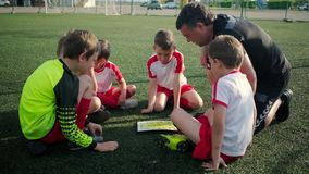 Football team of little boys and trainer are discussing a tactic. Small boys of football team and trainer are discussing a tactic on field on training stock footage
