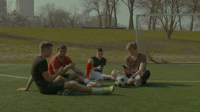 Football team with smart phones resting on soccer field stock footage