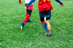Football teams - boys in red, blue, white uniform play soccer on the green field. boys dribbling. dribbling skills. stock image