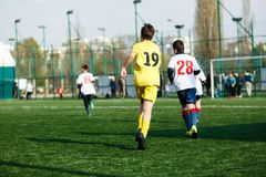 Football teams boys in yellow white sportswear play soccer on the green field. Dribbling skills. Team game, Training, stock photo