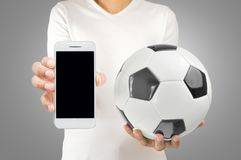 Football with technology. Cropped image of a young football player holding a soccer ball in one hand and the smartphone in another one wearing white tshirt over Royalty Free Stock Image