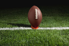 Football on tee at night ready for kickoff Royalty Free Stock Photo