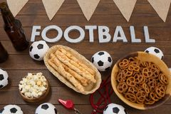 Football text and snacks on wooden table. Close-up of football text and snacks on wooden table Stock Image