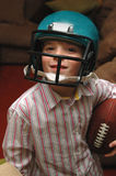 Football time. A smiling boy holding a football and wearing a helmet Royalty Free Stock Image