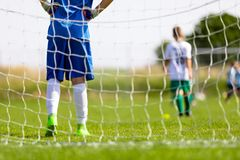 Football Training Game for Kids. Young Boy as a Football Goalkeeper Standing in a Goal. Soccer Players Running After the Ball in the Background. School Outdoor royalty free stock image