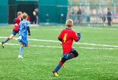 Football training for kids. Boys in blue red sportswear on soccer field. Young footballers dribble and kick ball in game. Training, active lifestyle, sport stock photo