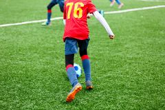 Football training for kids. Boys in blue red sportswear on soccer field. Young footballers dribble and kick ball in game. Training, active lifestyle, sport royalty free stock image