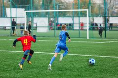 Football training for kids. Boys in blue red sportswear on soccer field. Young footballers dribble and kick ball in game. Training. Active lifestyle, sport royalty free stock photo