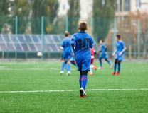 Football training for kids. Boys in blue red sportswear on soccer field. Young footballers dribble and kick ball in game. Training. Active lifestyle, sport royalty free stock photography