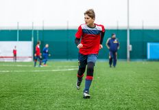 Football training for kids. Boys in blue red sportswear on soccer field. Young footballers dribble and kick ball in game. Training stock photos