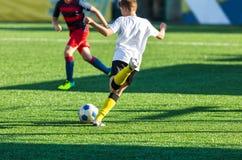 Football training soccer for kids. Boy runs kicks dribbles soccer balls. Young footballers dribble and kick football ball in game. Training, active lifestyle royalty free stock photo