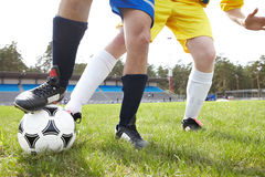 Football trick. Legs of footballer holding ball with forward behind Stock Photos