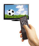 Football on TV. Male hand holding remote control to the TV screen with football on isolated on white stock photography