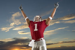 Football Victory. Football player celebrates victory and points at the sky in triumph stock image