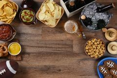 Football Watching Party Snacks and Drinks. Snacks and drinks laid out for a football watching party. Top view with copy space Royalty Free Stock Images