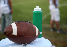 Football on water jug. A closeup view of an American football resting on the top of a water jug next to a sports water bottle Stock Photography