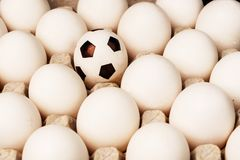 Football among the white eggs in the egg tray. royalty free stock photography
