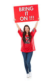 Football: Woman Holding Bring It On Sign Over Head. Pretty woman in football jersey ready for season Stock Photo