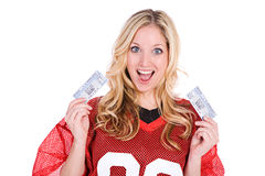 Football: Woman Holding TIckets To Game. Series with a woman in a football jersey, in various poses with a variety of props. Isolated on a white background stock image