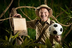 Football World Cup in Brazil. Smiling explorer in the jungle holding a soccer ball leaning to a sign Royalty Free Stock Photography
