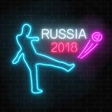 Football world cup 2018 in Russia neon glowing signboard on a dark brick wall background. Soccer world tournament sign with football player kicking a ball Stock Image