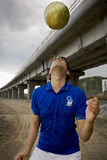 Football01. Guy playing football under a bridge royalty free stock image