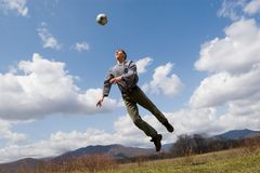 Footballer. The young man plays football on a lawn. Spring Stock Photography