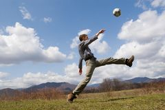 Footballer. The young man plays football on a lawn. Spring Royalty Free Stock Image
