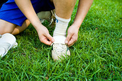 Footballer adjusting boot. Legs of footballer in shorts adjusting soccer boots on grass Stock Image