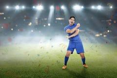 Footballer asiatique expressif après gain du match Photos stock