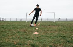 Footballer doing cone dribbling drill on field. Footballer moving the ball in between the cones practicing dribbling.  royalty free stock photos
