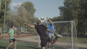 Footballer heading ball to score goal on pitch. Offensive soccer player jumping and heading ball to score goal after corner kick during football game on the stock footage