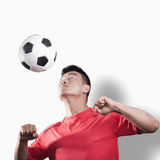Footballer heading the ball, white background Stock Photography