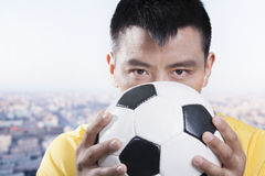 Footballer holding ball against his face Royalty Free Stock Photo