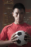 Footballer holding ball to chest with skyscraper on the background Royalty Free Stock Photos