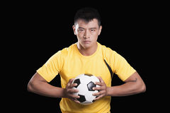 Footballer player holding ball to chest, black background Stock Photo