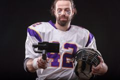 Footballer with smartfone on gimbal. American footballer online in social networks using a mobile phone on the stabilizer from studio stock image