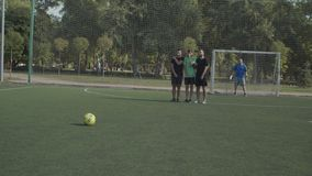 Footballer taking a free kick during football game. Soccer player making direct free kick in attempt to score a goal during football game on pitch. Defending stock video footage