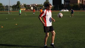 Soccer player is training and bouncing a soccer ball by his foot. Footballer is training and bouncing a soccer ball on his leg, white and red T-shirt stock video