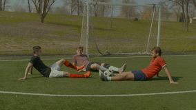 Footballers relaxing on soccer field after game stock video footage