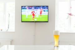 Footballeur à la télévision et à un verre de bière de blé sur une table Photographie stock libre de droits
