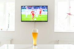Footballeur à la télévision et à un verre de bière de blé sur une table Photos stock