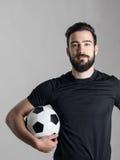 Footballeur barbu de sourire amical tenant la boule sous son bras regardant l'appareil-photo photographie stock libre de droits