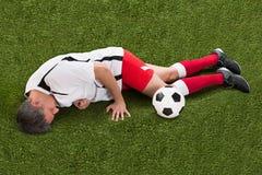 Footballeur blessé se trouvant sur l'herbe photographie stock