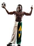 Footballeur brésilien d'homme de couleur tenant montrer le football  Image stock