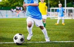 Footballeur courant Match de football du football d'enfants Le football de jeu d'enfants Photographie stock libre de droits