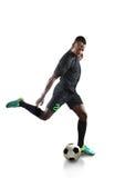 Footballeur d'afro-américain donnant un coup de pied la boule images stock